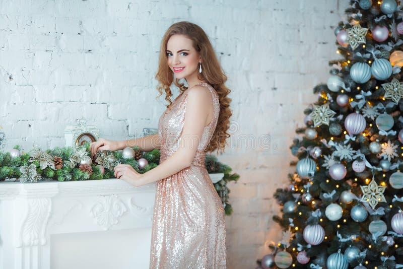 Feiertags-, Feier- und Leutekonzept - junge Frau im eleganten Kleid über Weihnachtsinnenraumhintergrund Bild mit lizenzfreie stockfotos