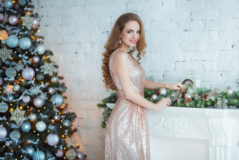 Feiertags-, Feier- und Leutekonzept - junge Frau im eleganten Kleid über Weihnachtsinnenraumhintergrund Bild mit stockfoto