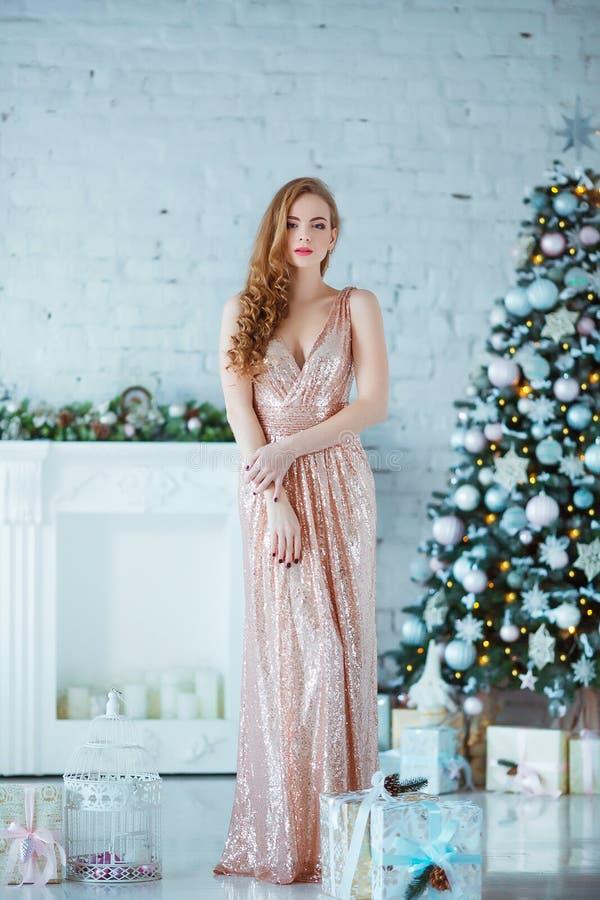 Feiertags-, Feier- und Leutekonzept - junge Frau im eleganten Kleid über Weihnachtsinnenraumhintergrund Bild mit lizenzfreie stockfotografie