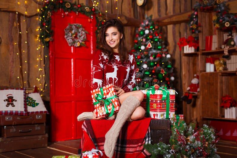 Feiertags-, Feier- und Leutekonzept - junge lächelnde Frau in der roten Strickjacke, die Weihnachtsgeschenk über Weihnachtsinnenr stockbilder