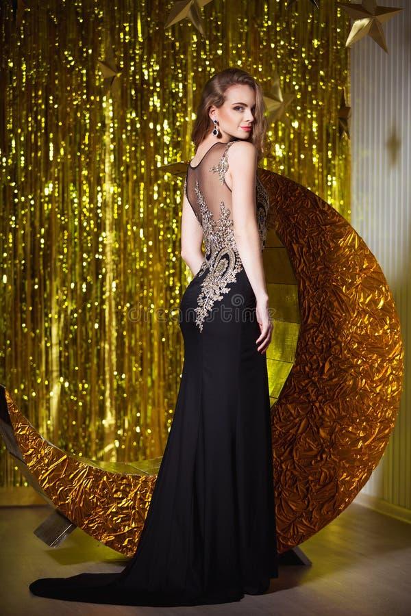 Feiertags-, Feier- und Leutekonzept - junge lächelnde Frau im eleganten Kleid über festlichem Innenhintergrund stockbilder