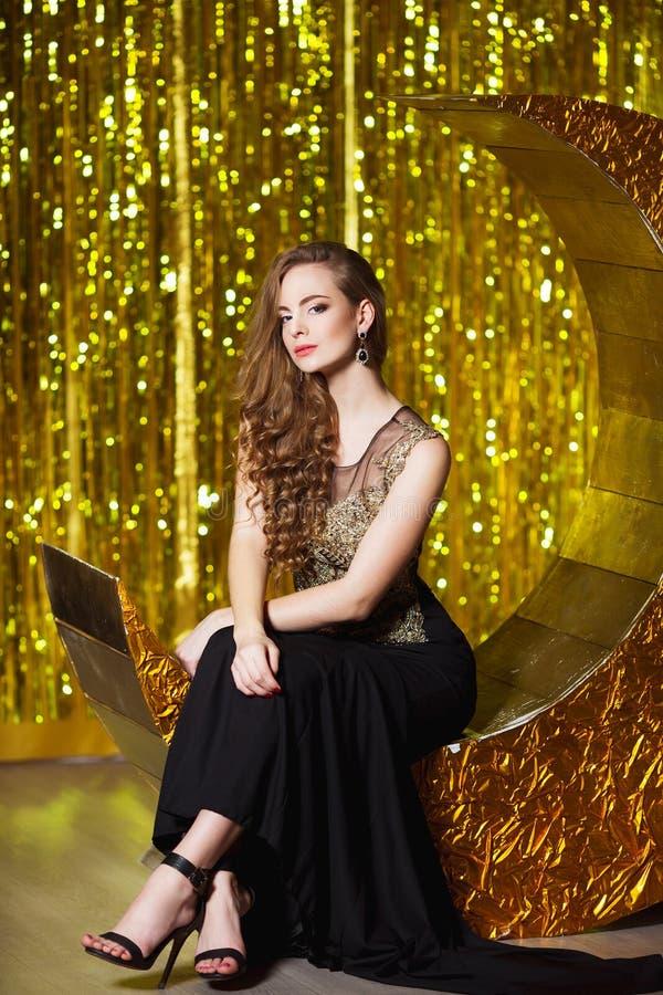 Feiertags-, Feier- und Leutekonzept - junge lächelnde Frau im eleganten Kleid über festlichem Innenhintergrund stockbild