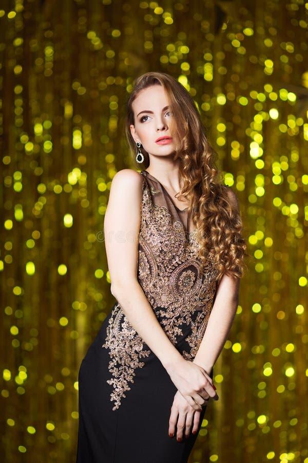 Feiertags-, Feier- und Leutekonzept - junge lächelnde Frau im eleganten Kleid über festlichem Innenhintergrund lizenzfreies stockfoto