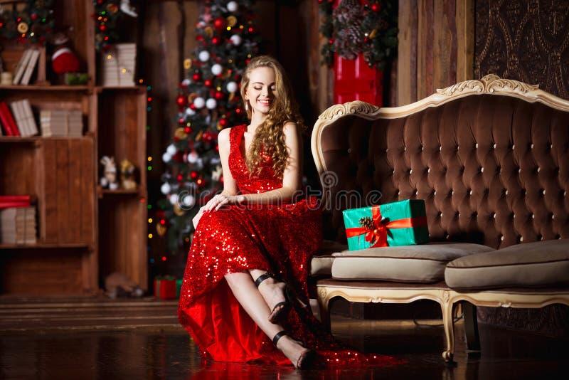 Feiertags-, Feier- und Leutekonzept - junge lächelnde Frau im eleganten roten Kleid über Weihnachtsinnenraumhintergrund lizenzfreie stockbilder