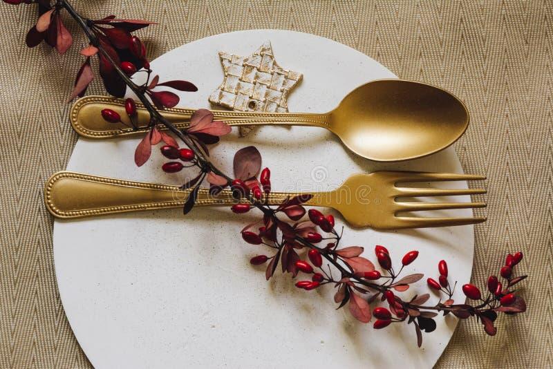 Feiertags-Goldgedeck, weiße Platte des Betons, mit Gabel und goldenem Löffel Weihnachten oder tanksgiving Abendessen Von oben lizenzfreie stockfotos