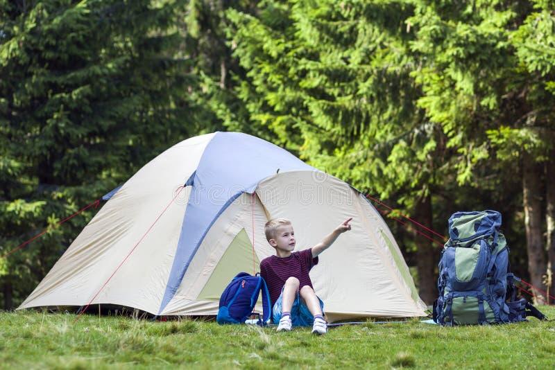 Feiertags-Kampieren Junge, der vor einem Zelt nahe backp sitzt stockfotografie