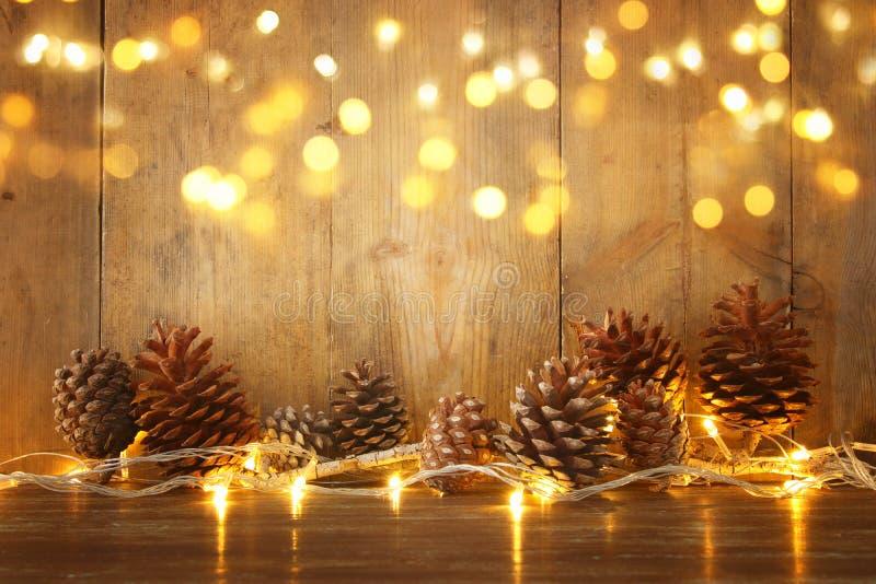 Feiertagsbild mit Weihnachtsgoldenen Girlandenlichtern und Kiefernkegeln über hölzernem Hintergrund stockfoto