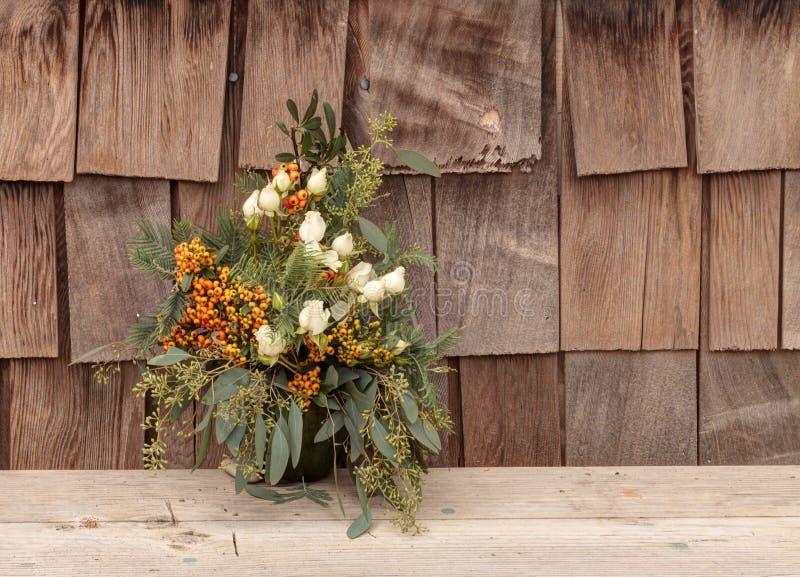 Feiertagsblumenblumenstrauß innerhalb eines Kürbisvase stockfoto