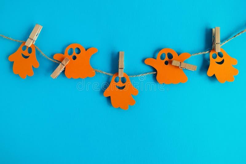 Feiertagsdekorationen für Halloween Orange Papiergeister, die an einem Seil auf einem blauen Hintergrund mit Kopienraum hängen lizenzfreie stockfotografie