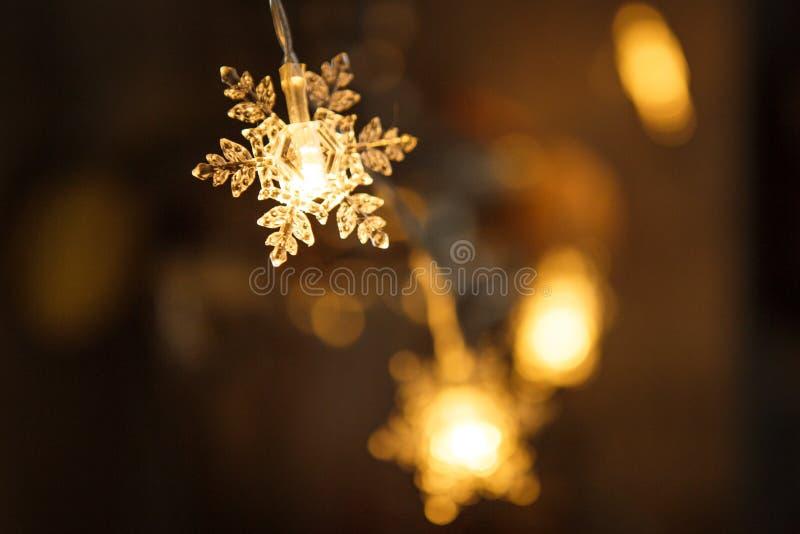 Feiertagsgirlande, klare Plastikschneeflocke glüht mit einem goldenen Licht stockfotos