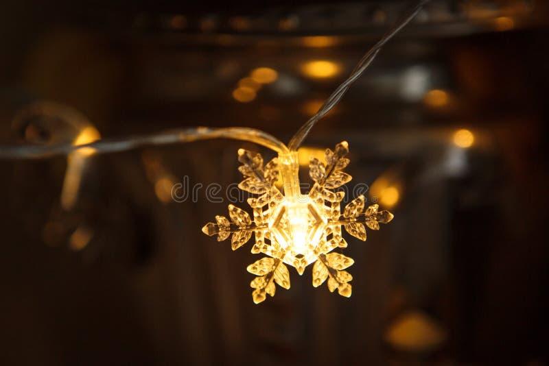 Feiertagsgirlande, klare Plastikschneeflocke glüht mit einem goldenen Licht stockfoto