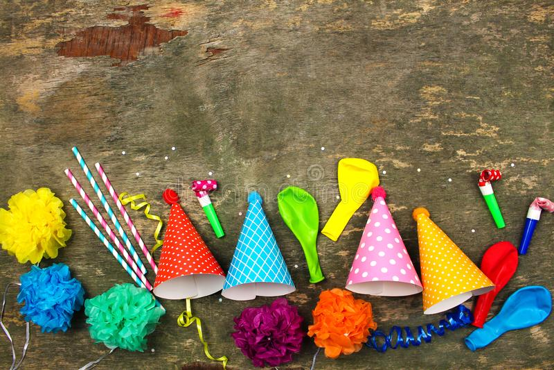 Feiertagshüte, Pfeifen, Ballone auf altem hölzernem Hintergrund Konzept von Kind-` s Geburtstagsfeier lizenzfreie stockfotos