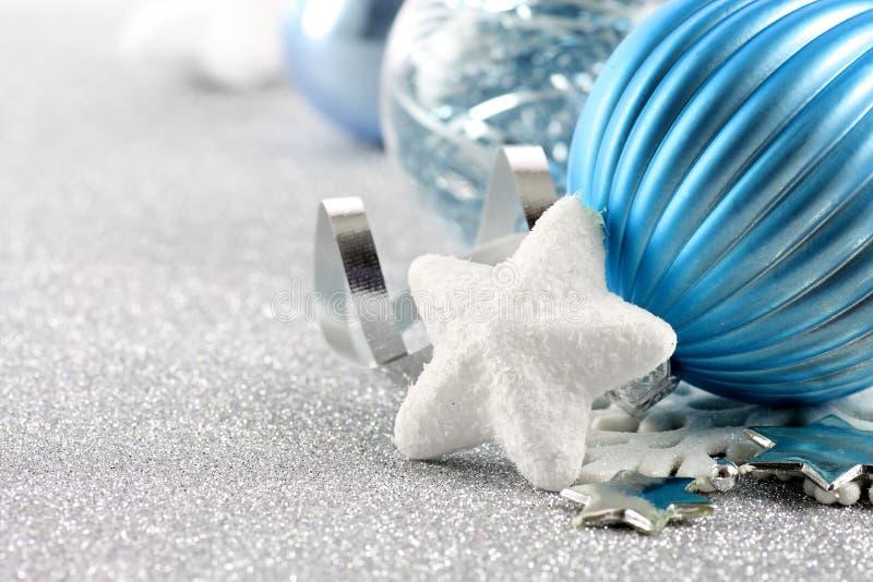 Feiertagshintergrund mit weißer Schneeflocke und blauen Weihnachtsverzierungen lizenzfreie stockfotografie