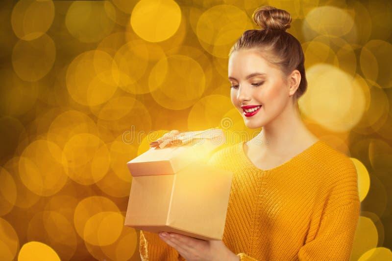 Feiertagskonzept über Lichthintergrund Frau, die ein Geschenk anhält stockfotografie