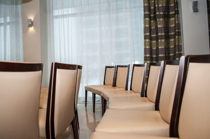 Feiertagskonzept, luxuriöse Holzstühle mit beige Polsterung sind in der Aula stockbild