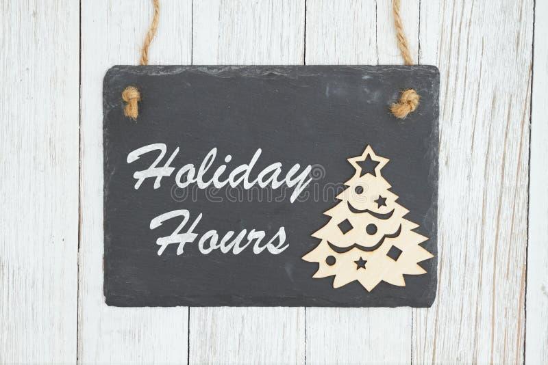 Feiertagsstunden unterzeichnen auf Tafel mit Weihnachtsbaum lizenzfreies stockfoto