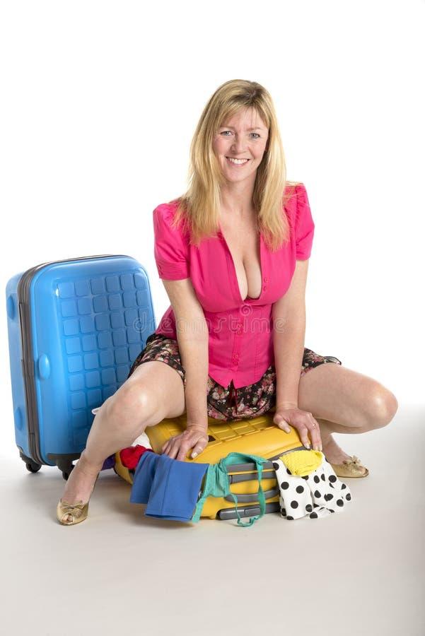 Feiertagsverpackungsfrau, die auf Koffer sitzt lizenzfreies stockbild