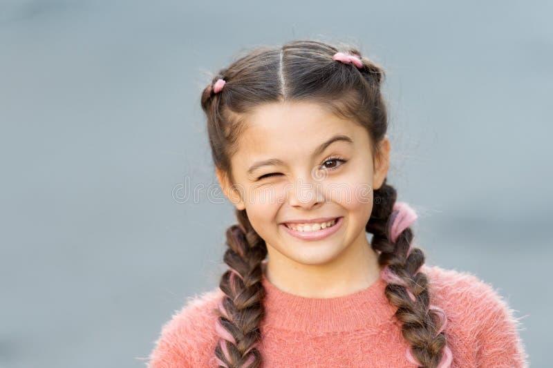 Feignez et plaisanterie Expression gaie d'enfant espiègle Choses allant être bien Fond gris de visage gai de clin d'oeil de fille photo libre de droits