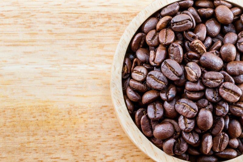 Feijão de café Roasted na bacia de madeira na opinião superior da textura de madeira com fotografia de stock royalty free
