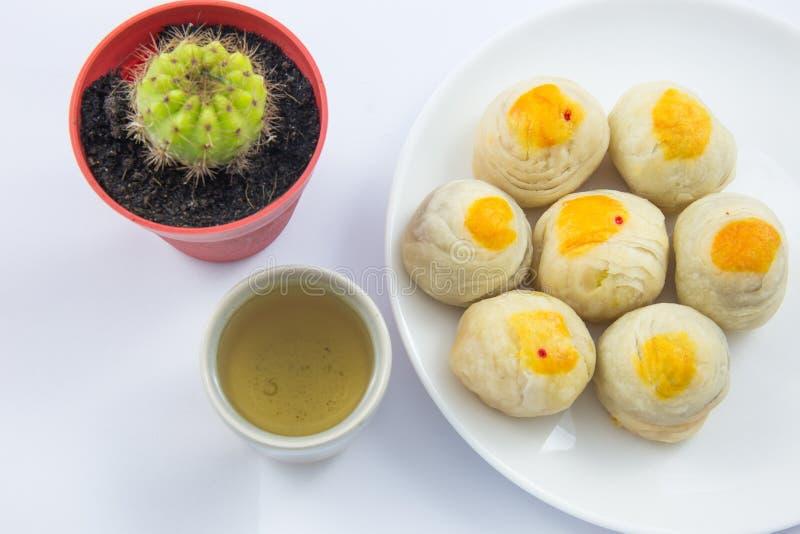 Feijão de Mung da pastelaria ou Mooncake chinês com gema no copo do prato e de chá verde foto de stock