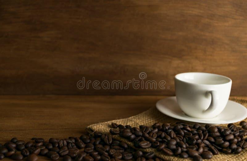 Feijão e xícara de café de café na placa de madeira na frente do marrom fotografia de stock royalty free