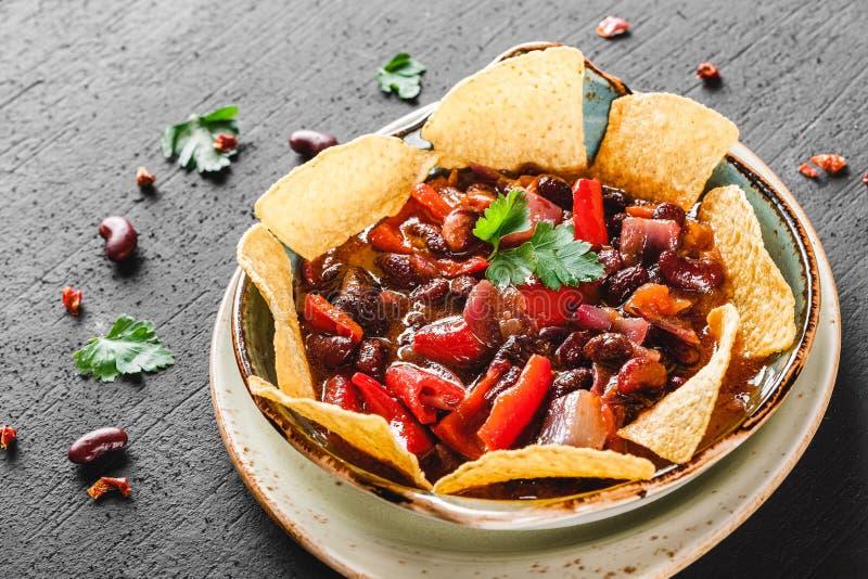 Feijão vermelho com nachos ou microplaquetas do pão árabe, pimenta e verdes na placa sobre o fundo escuro Petisco mexicano, alime fotografia de stock royalty free