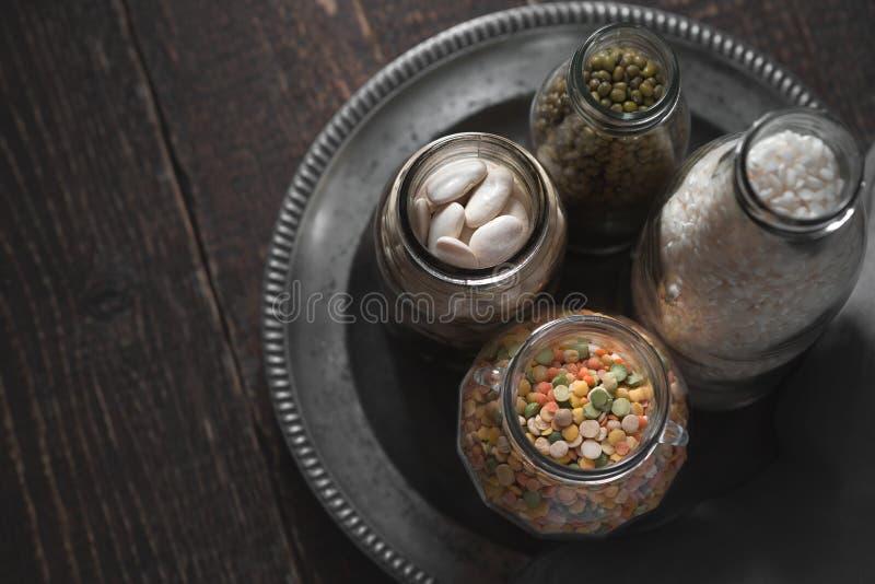 Feijões brancos, feijões verdes, lentilhas e arroz em umas latas em um fundo escuro imagens de stock