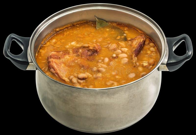 Feijões com os reforços de carne de porco fumado cozidos em Saucepot de aço inoxidável velho isolados no fundo preto fotos de stock