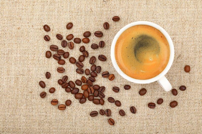 Feijões completos do copo e de café do café na lona fotos de stock royalty free