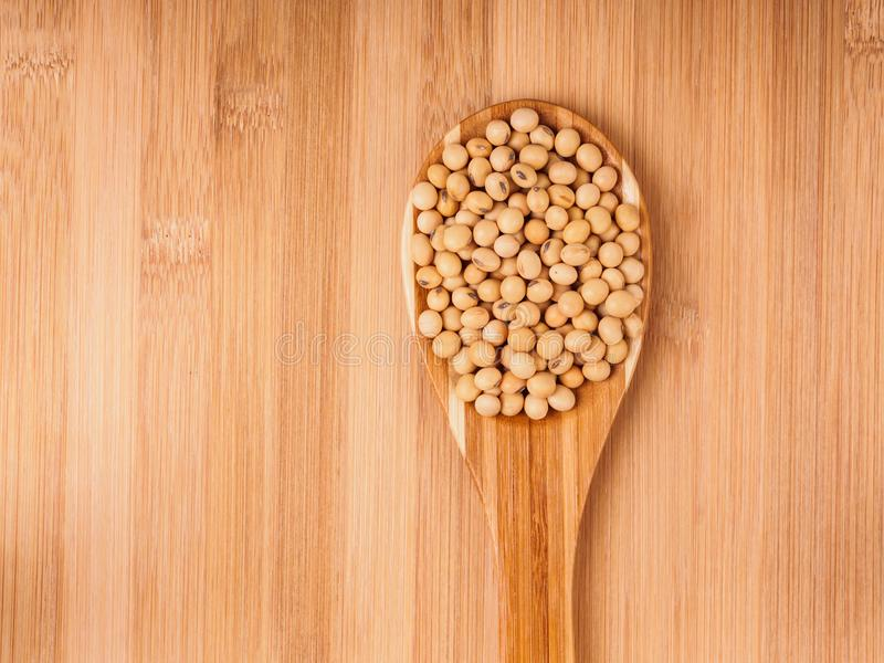 Feijões da soja na colher de madeira imagens de stock