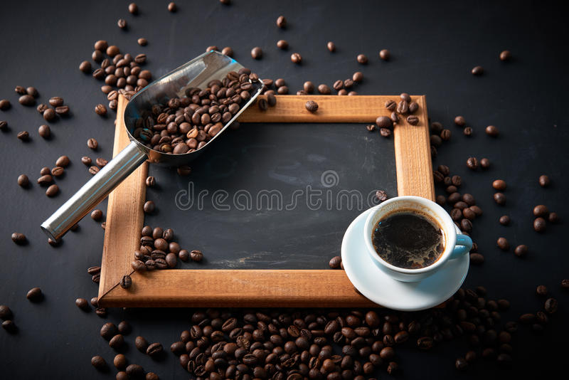 Feijões da xícara de café e de café em um fundo preto Vista de acima placa preta com espaço da cópia imagem de stock