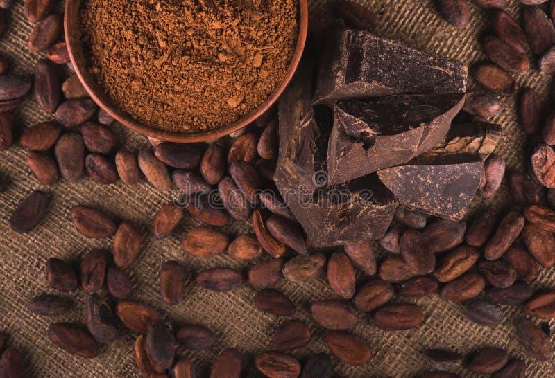 Feijões de cacau crus, bacia da argila com pó de cacau, chocolate no saco foto de stock royalty free