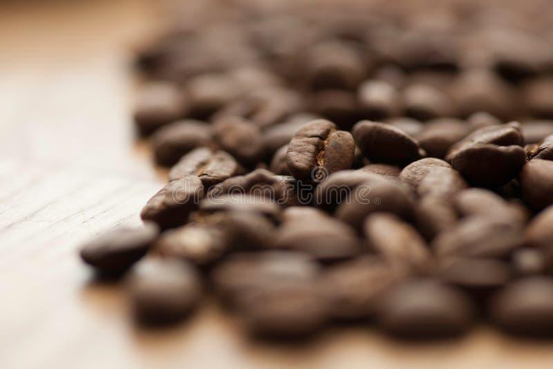 Feijões de café aromáticos na tabela - macro - close up imagem de stock royalty free