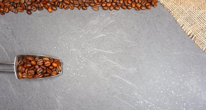 Feijões de café de comércio justos com serapilheira e colher no fundo cinzento do worktop da cozinha fotografia de stock royalty free