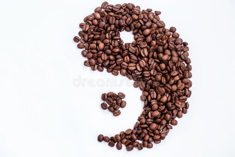 Feijões de café de Brown na forma de um Yin e de um Yang em um fundo branco fotos de stock royalty free