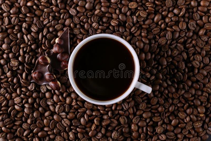 Feijões de café dispersados, um copo e chocolate preto imagens de stock