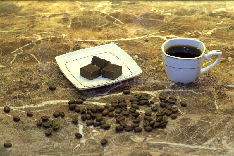 Feijões de café do chocolate do café em uma tabela de mármore foto de stock