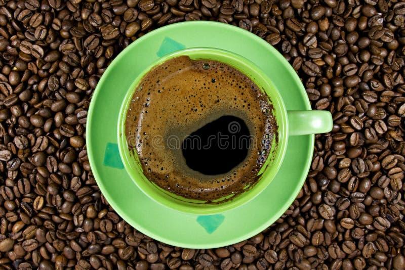 Feijões de café e copo verde fotografia de stock royalty free