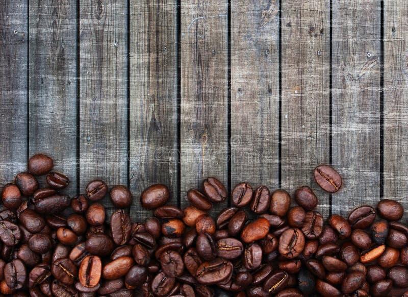 Feijões de café e fundo de madeira imagens de stock