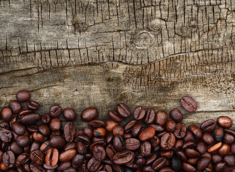 Feijões de café e fundo de madeira fotografia de stock royalty free