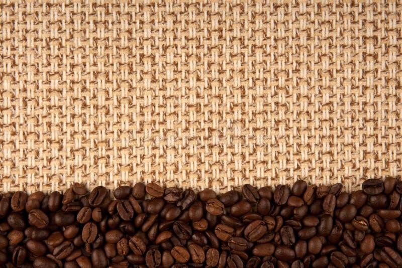 Feijões de café e fundo do sackcloth foto de stock