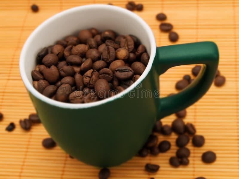 Feijões de café em um copo verde imagem de stock royalty free