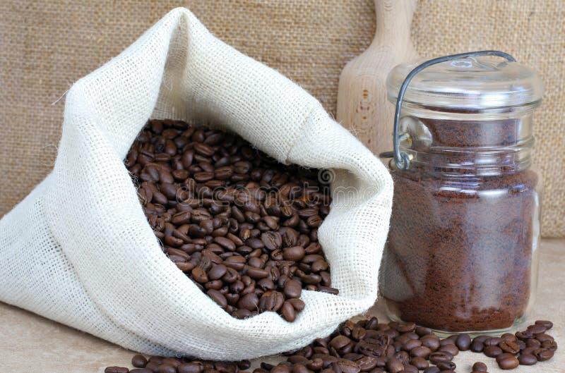 Feijões de café em um saco e em um frasco imagens de stock royalty free