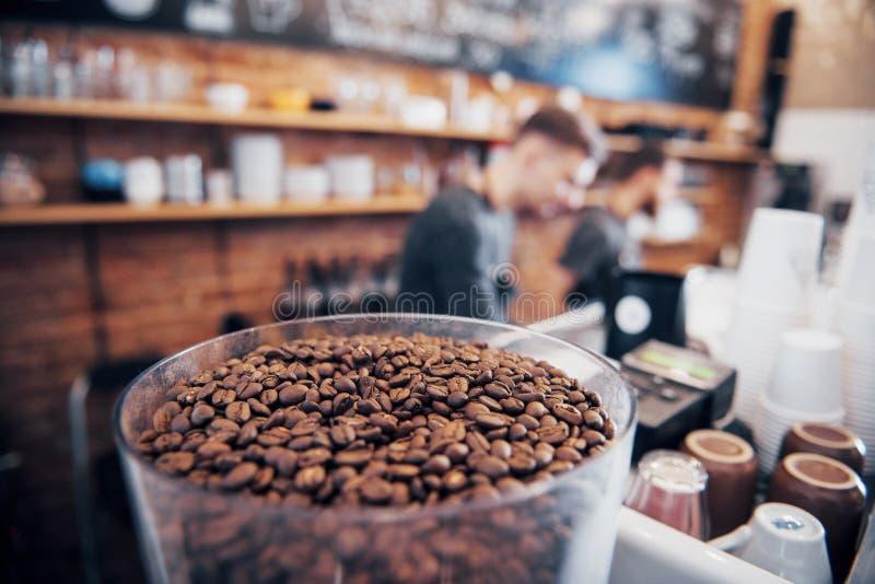 Feijões de café escuros e aromáticos em uma máquina moderna da repreensão com a imagem borrada do torrificador de café profission fotografia de stock
