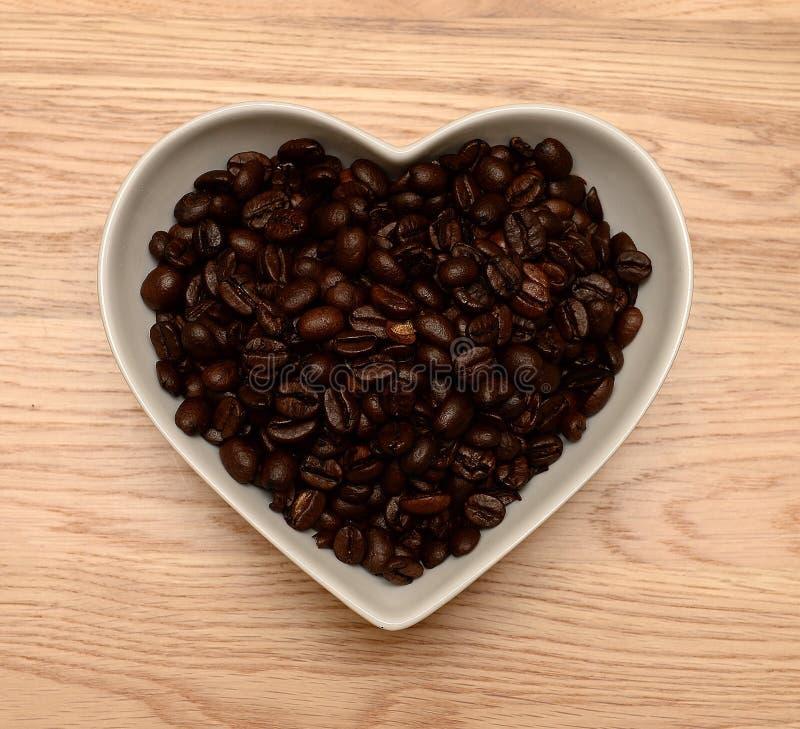 Feijões de café na bacia dada forma coração imagem de stock royalty free