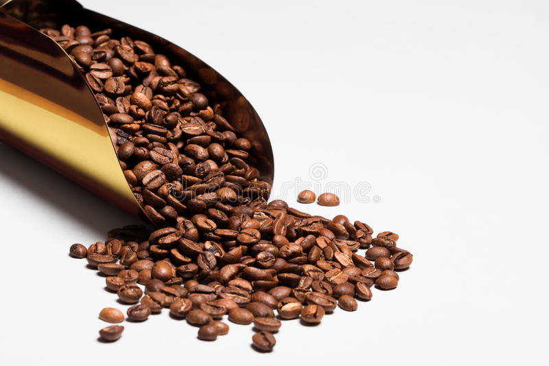 Feijões de café na colher dourada na tabela branca Espaço para o texto imagem de stock