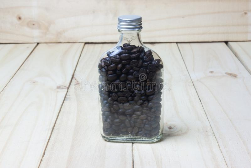 Feijões de café na garrafa de vidro no fundo de madeira fotos de stock royalty free