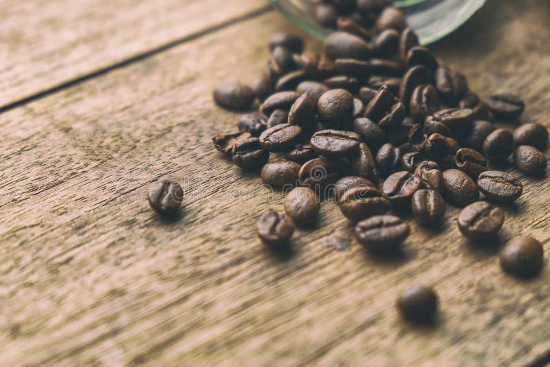 Feij?es de caf? na tabela de madeira velha Imagem retro do estilo do vintage adicionada fotos de stock royalty free
