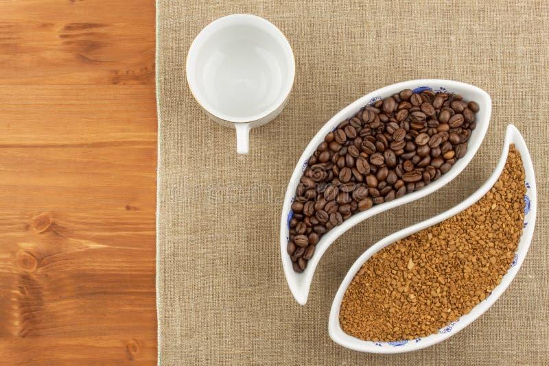 Feijões de café naturais contra o instante Feijões do solúvel e de café no fundo de madeira Preparando o café fresco imagens de stock royalty free