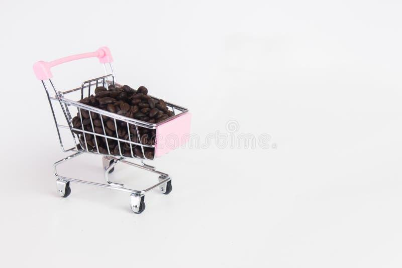 Feijões de café no carrinho de criança no fundo branco fotos de stock